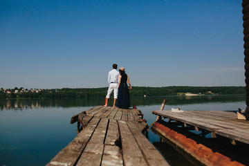 Hugging man and woman in love on wooden pier