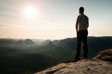 Satisfy tall hiker in grey shirt and dark trousers. Sprtsman on the peak of sharp rock edge  watching down to landscape.
