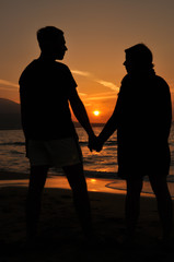 Silhouettes of a couple keeping hands in the sunset