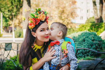 Small boy kissing his mother  in the cheek
