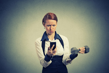 angry business woman reading news e-mail on mobile phone lifting dumbbell