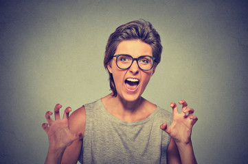 Angry young woman with glasses screaming