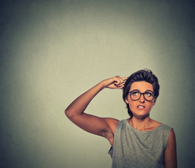 Contused thinking woman with glasses bewildered scratching her head