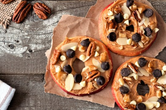 Apple rounds with peanut butter, chocolate chips and nuts, downward view on paper with rustic wood background