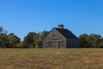 New England rustic barn in summer with a green grass lawn