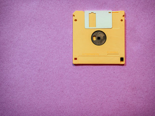 Vintage yellow floppy disk on Magenta background
