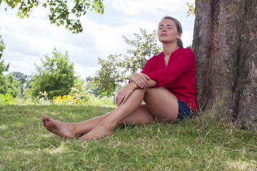 thinking young woman enjoying summer freshness under a tree
