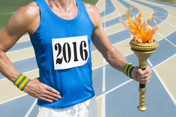 Athlete wearing 2016 race bib holding sport torch in front of running track