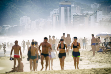 Busy crowded afternoon on Ipanema Beach during a misty sunset in Rio de Janeiro Brazil