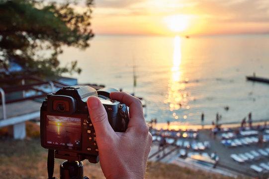Photographer takes photos of beautiful sunset