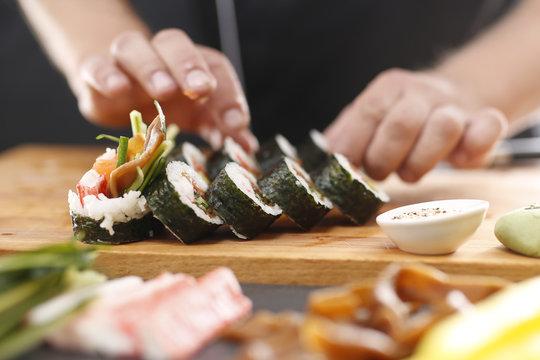 Sushi master przyrządza futomaki z łososiem, krewetką i ogórkiem