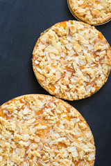 Homemade tarts with apricot jam and almond slices baked in different sizes