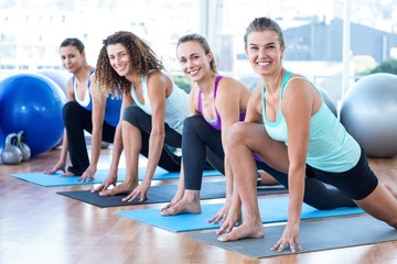 Fit women in fitness studio doing high lunge pose Wall mural