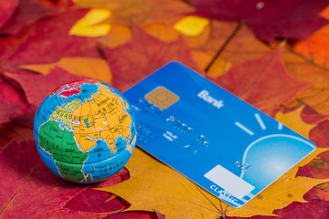 credit card and small globe with Europe, Africa, Asia on the bac