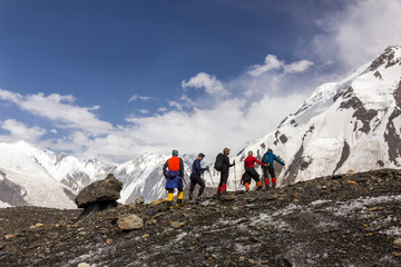 Mountaineers Walking Across Large Glacier Group of Mountain Climbers with High Altitude Boots and Clothing Crossing Glacier Surface with Unusual Rock Mushroom on Foreground and Blue Sky background