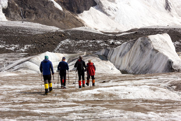Mountaineers Walking Across Large Glacier Group of Mountain Climbers with High Altitude Boots and Clothing Crossing Ice Section During Ascent of Alpine Expedition in Asia Mountain Area