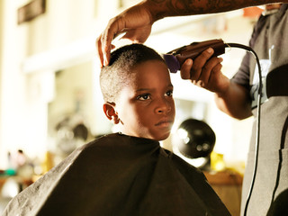 little african boy getting his hair cut in barber shop
