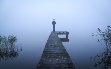 Man standing on a jetty at a lake during a foggy, gray morning. Wall mural