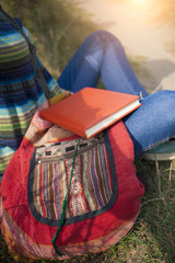Traveller girl sitting with a book on nature.