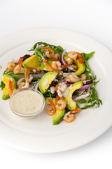 Salad with avocado and shrimp on the white background vertical