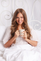 Beautiful woman relaxing in the bed with a cup of tea