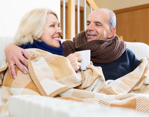 Spouses under blanket drinking tea