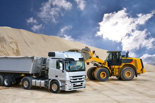 Transportwesen: Verladung von Sand in einem Kieswerk mit Radlader // Construction: loading of sand in a gravel pit with loaders