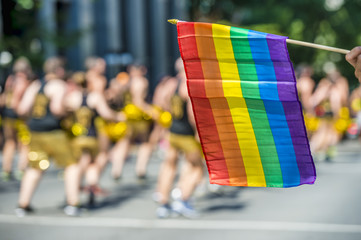 Rainbow flag floating in front of blurred gay dancers