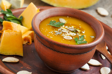 Pumpkin soup with oil and seeds in a clay bowl in a rustic style