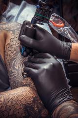 Professional tattooist showing process of making a tattoo in tattoo studio