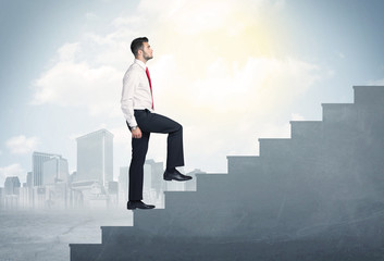 Businessman climbing up a concrete staircase concept