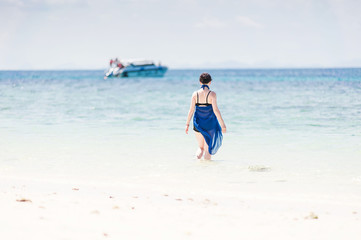 Girl walking in the sea at white sand beach