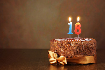 Birthday chocolate cake with burning candles as a number eighteen on brown background
