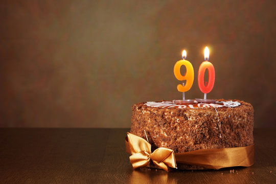 Birthday chocolate cake with burning candles as a number ninety on brown background
