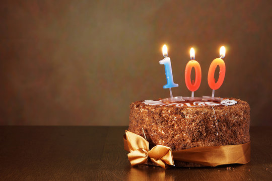 Birthday chocolate cake with burning candles as a number one hundred on brown background