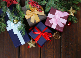 gift boxes with festive ribbons and Christmas decorations on a wooden background
