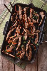 Korean Food: Bulgogi beef with carrot on grill pan closeup. Vertical top view
