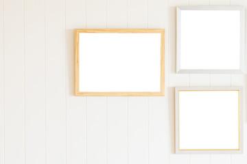 Blank photo frame on white wood wall background