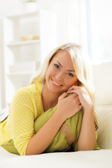 Young and happy woman resting on sofa at home