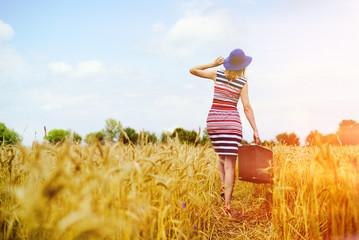 Girl in blue hat walking away in golden sunlight countryside