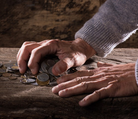 Close up of  caucasian old man's hands  and pile of old coins on a wooden background