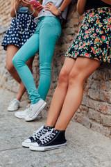 Three pretty girls leaning against a wall