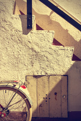 Retro wheel bicycle detail and old stairs. Vintage style.