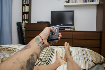 Young man lying on bed watching television. Self POV