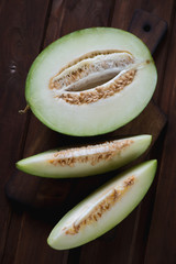 Above view of sliced cantaloupe melon, dark brown wooden surface