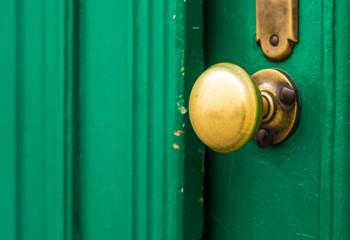 Weathered doorknob made of brass on green door Wall mural