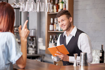 Attractive male bartender is serving female customer