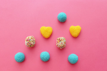 Blue and yellow heart shaped candy on pink background