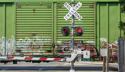 railroad crossing sign with train passing behind