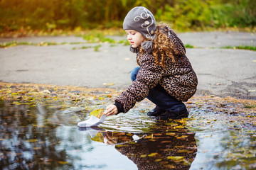 Girl runs a paper boat in the autumn park.